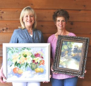"Kathryn Fisher holding her piece entitled ""Lilies and Lemons en Plein Air""; Regina Willard holding ""Texas Creek Bend"""